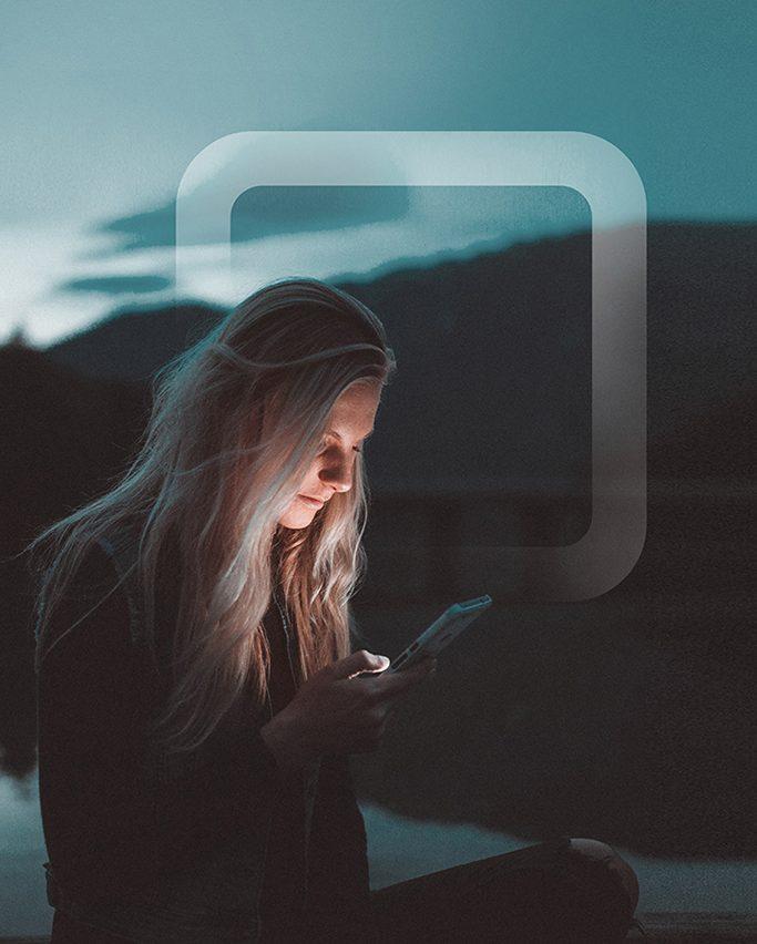 En ung tjej i ett mörkt landskap med en mobiltelefon