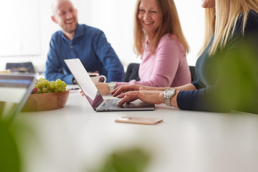 Tre medarbetare skrattar, en dator är i bildfokus, kontorsmiljö