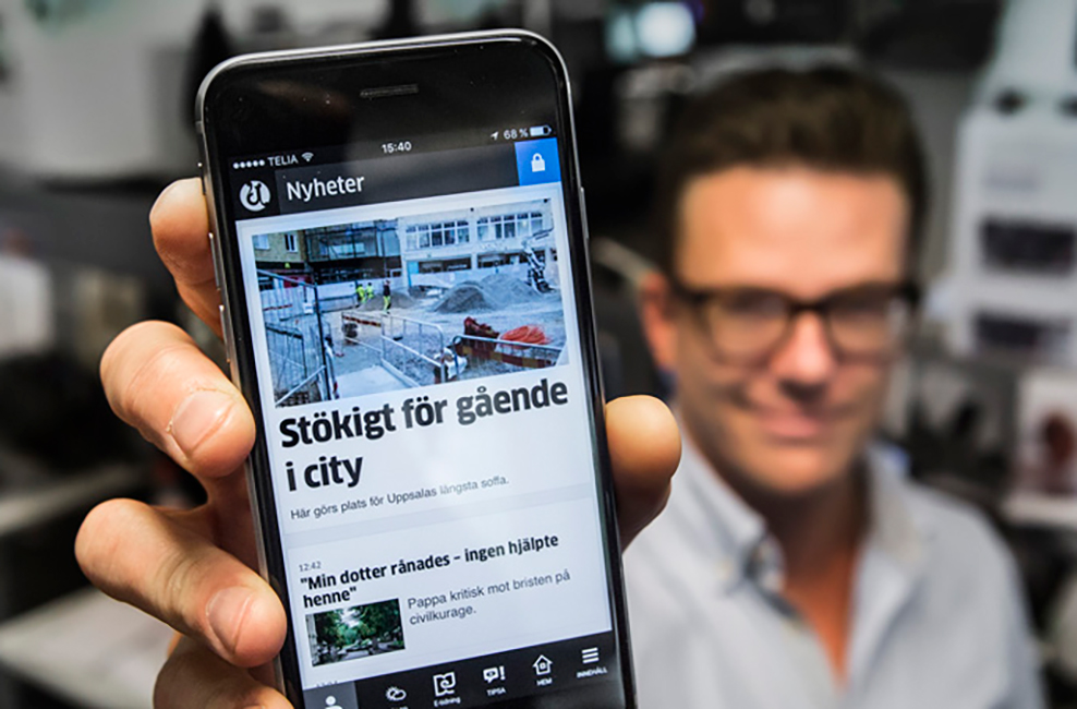 Man håller i mobiltelefon som visar UNTs nyhetsflöde